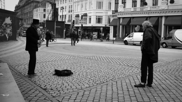 A saxophone player captures the attention of a local homeless person as he walks by. Although Denmark is a welfare state, there are still a small handful of citizens who are homeless.