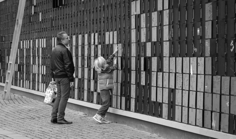 "A father stands watch as his son turns over colored tiles along Copenhagen's ""Happy Wall"", which is an outdoor art exhibit that uses pedestrian created art to cover up the unsightly views of a construction site."